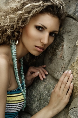 Fashion portrait of young beautiful woman against stone wall photo