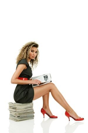 Young woman reading glossy magazines sitting on stack of it isolated over white background Stock Photo - 8703342