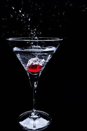 martini splash: Red berry droping into cocktail with splashing over dark background Stock Photo