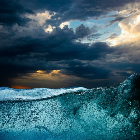 Blue water wave against dramatic storm clouds