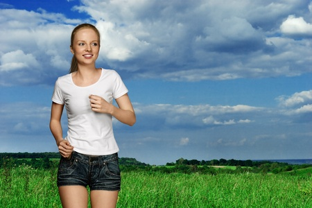 Running young woman in white shirt on dark background photo
