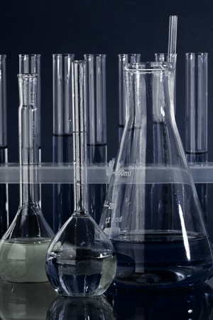 Laboratory glassware test tubes and vial with blue liquid on blue background photo