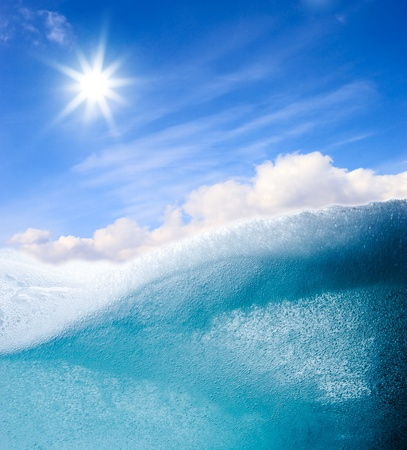 Turquoise water wave abstract background with bright sun on blue sky Stock Photo