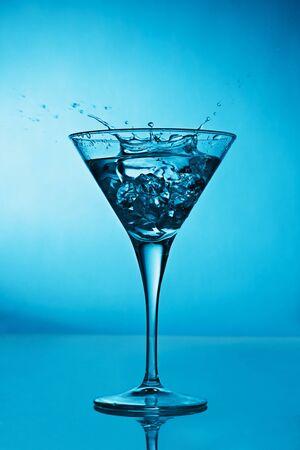 verm�: Vermut c�ctel dentro de la Copa de martini sobre fondo azul Foto de archivo