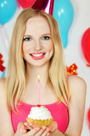 Young blond girl celebrating birthday holding cake with candle in hands photo