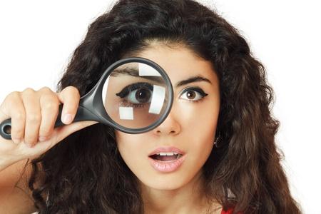 lupa: Chica sorprendida mirando a trav�s de la lupa Foto de archivo
