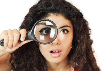 Surprised girl looking through magnifying glass photo