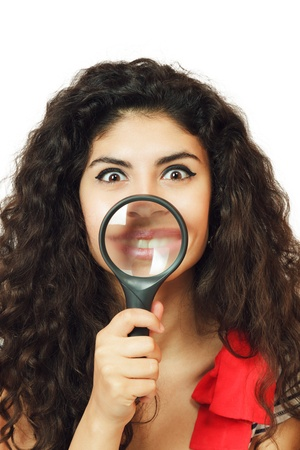 Young woman showing lips through magnifying glass photo
