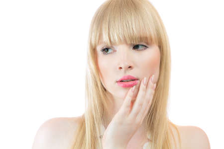 sidewards: Attractive young blond woman touching skin on cheek isolated over white background