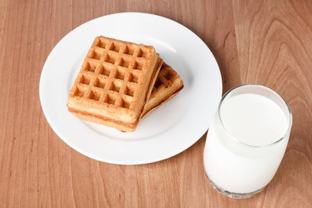 Belgian waffles and cup with milk layed on wooden tabledesk photo