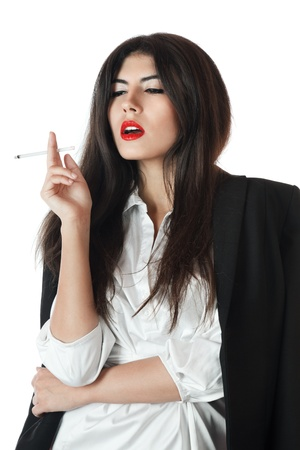 Young businesswoman smoking a slim cigarette with pleasure photo