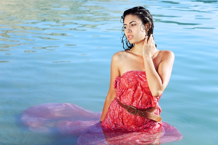 sidewards: Sexy young woman in wet dress posing in water Stock Photo