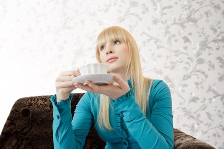 sidewards: Young blonde woman with tea cup sitting on sofa and thinking looking up