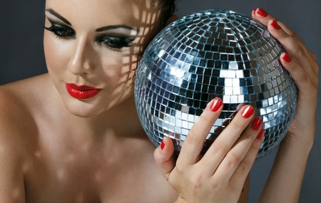 Close-up face of young woman with fashionable make-up and disco ball in hands photo