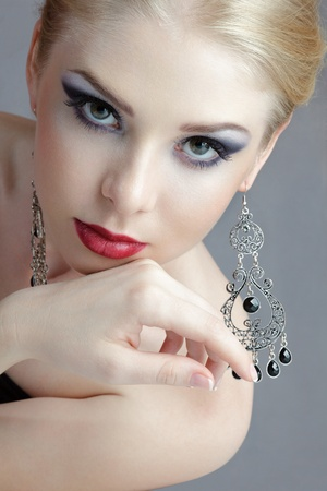 Beautiful young blonde woman with ornate earrings looking to camera studio shot
