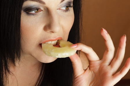 sidewards: Young woman bitting pineapple ring looking sidewards