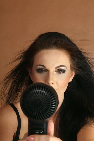 young woman drying her hair electric hair dryer photo