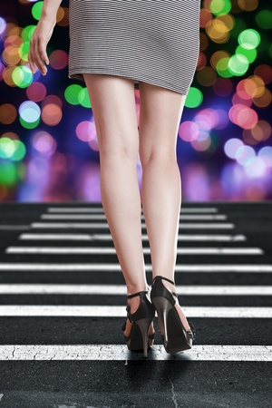 crosswalk: Beautiful young woman with long legs in mini dress rear view Stock Photo