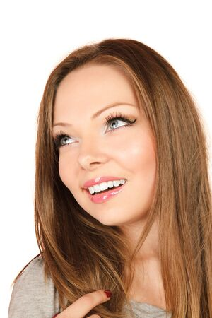 sidewards: Young smiling woman looking up and sidewards Stock Photo