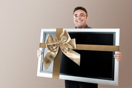 Man holding in hands lcd tv with flat screen and golden bow photo