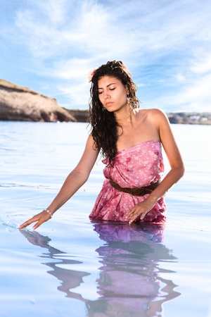 wet dress: Young sexy woman in pink dress posing in water ad sea beach