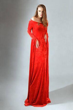 vestido medieval: Joven mujer posando en vestido rojo de estilo victoriano Foto de archivo