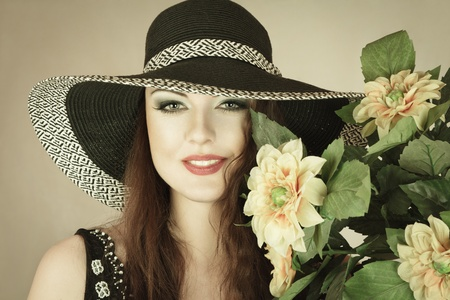 Young woman in sun hat with bouquet of yellow flowers photo