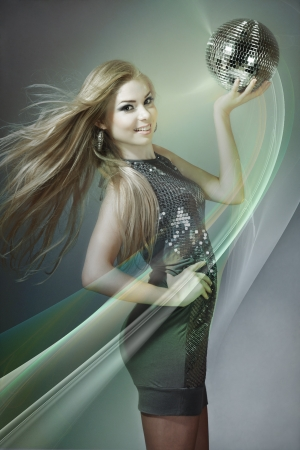 Blond woman dancing with disco ball photo