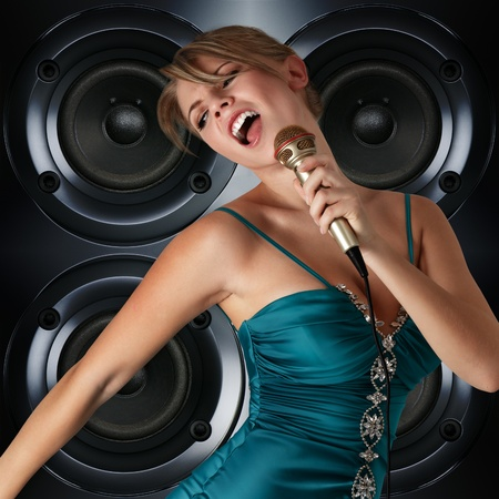 Beautiful young woman with microphone against wall of speakers