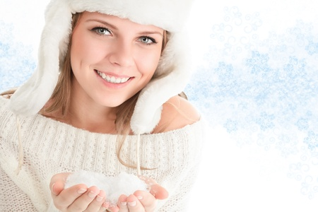Beautiful young woman in white hat and snow in hands photo