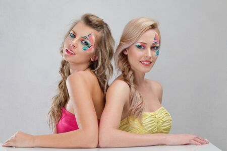 Two girls with creative make-up sitting back to back Stock Photo - 11498415