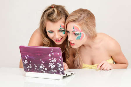 Two surprised young women reading e-mail message from laptop computer Stock Photo - 11498440