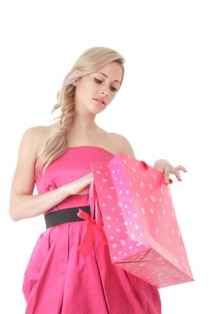Mujer rubia joven que mira en la bolsa de compras aisladas sobre fondo blanco