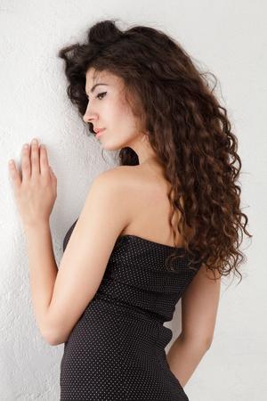 cabello rizado: Mujer joven con el pelo largo y rizado posando cerca la pared