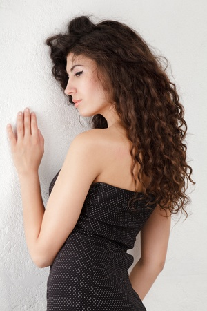 Young woman with long curly hair posing near wall