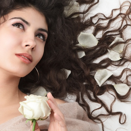 Woman with long hair lying down on back with white rose petals photo