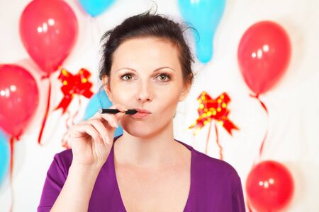 Woman with electronic cigarette against decorated wall photo