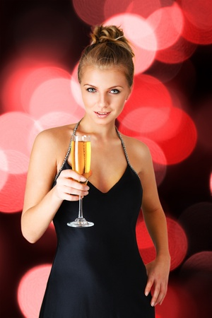 Young woman in black elegant dress holding goblet with champagne photo