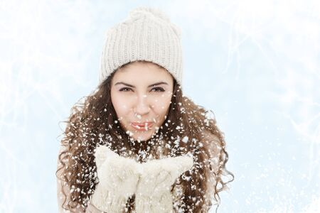 winter woman: Young woman blowing snowflakes from hands