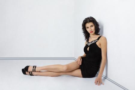 falda corta: Atractiva mujer joven en vestido corto negro sentado en el piso cerca de la pared