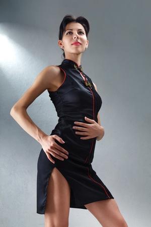 mini falda: Hermosa mujer joven en el estudio de negro mini vestido disparo
