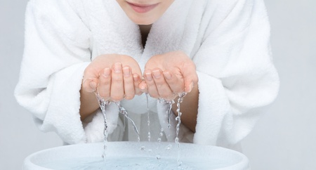 Young woman in white bathrobe washing face