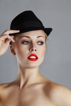 sidewards: Young blond woman in black hat looking sidewards