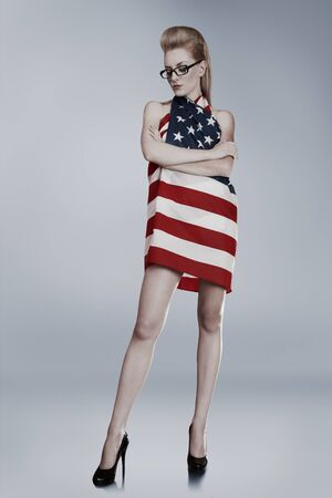 Young attractive blond woman wrapped in american flag photo
