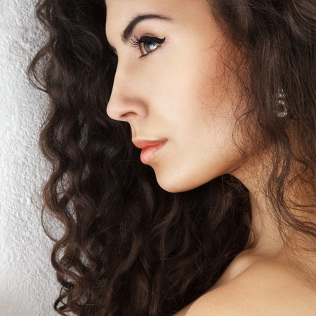 sidewards: Close-up portrait of young beautiful woman with long curly hair