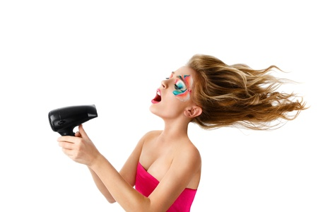 woman flying: Young blonde woman drying hair with electric fan Stock Photo