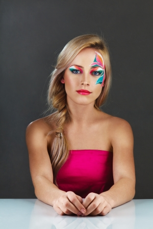 Beautiful young blonde woman with fantasy flowers creative make-up studio shot photo