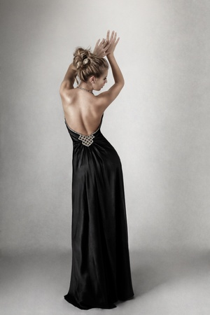 personas de espalda: Mujer joven rubia en el abierto de nuevo elegante vestido negro Foto de archivo