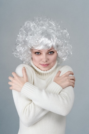 Emotional young frozen blonde woman in white sweater Stock Photo - 12285751