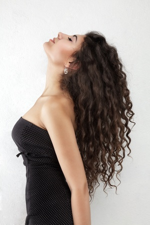 wild hair: Side view portrait of young beautiful woman with long curly hair
